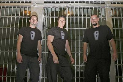 photo shows the ghost adventures crew standing in front of a jail cell in the dark