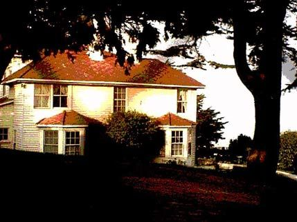 Photo shows the façade of the Haskell House, with a red roof and large trees framing it. It has two bay windows that overlook the shores of San Francisco bay