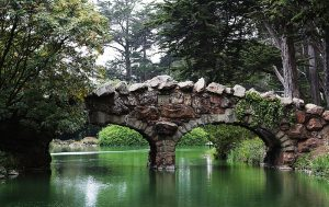 Photo shows a rock bridge crossing over the waters of Stow Lake. Trees surround the bridge and lake.