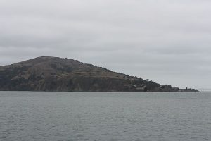 Photo shows Angel Island covered with a blanket of clouds, dark and dreary. It sits in the middle of San Francisco Bay.